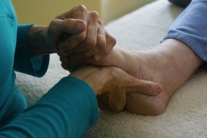 Jennifer Frick, Portland, Maine, applying Reflexology to a client's foot.
