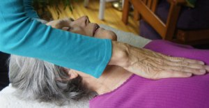 Jennifer Frick, Portland, Maine, giving Reiki to a client.